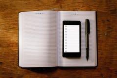 Telefon komórkowy na otwartym czasopiśmie lub dzienniczku Fotografia Stock