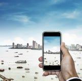 Telefon komórkowy na ręce z pejzażu miejskiego niebieskim niebem i widokiem Zdjęcie Stock