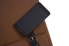 Telefon komórkowy na rzemiennej torbie Zdjęcie Stock
