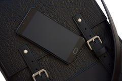 Telefon komórkowy na rzemiennej torbie Obrazy Stock
