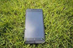 Telefon komórkowy na trawie obraz stock