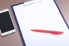 Telefon komórkowy, pióro i falcówka na drewnianym tle, Zdjęcie Stock