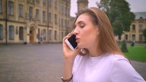 Telefon komórkowy rozmowa caucasian dziewczyna która stoi na ulicie i opowiada z koncentracją,