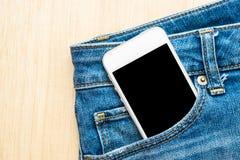 Telefon komórkowy w niebieskich dżinsach spodniowych na drewnianym tle Zdjęcia Royalty Free