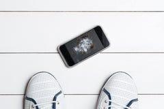 Telefon komórkowy z łamanym ekranem na drewnianej podłoga Obrazy Royalty Free