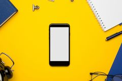 Telefon komórkowy z białym notepad, błękitnym notatnikiem i piórem na żółtym tle, fotografia stock