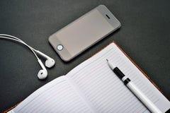 Telefon, Kopfhörer, Tablette und Notizblock Lizenzfreie Stockfotos