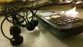 Telefon med hörlurar med mikrofon Fotografering för Bildbyråer