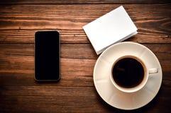 Telefon med lögner för en kopp kaffe och vitbokpå en träbakgrund arkivfoton