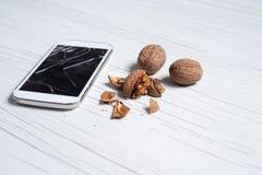 Telefon mit defektem Glas und den Walnüssen lizenzfreie stockfotos