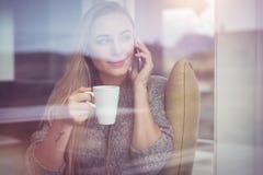 Am Telefon mit Tasse Tee Stockfotos