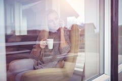 Am Telefon mit Tasse Tee Lizenzfreie Stockfotografie