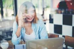 Telefon och arbete för ung hipsterkvinna talande på coffee shop Royaltyfri Bild