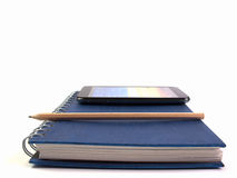 Telefon och blyertspenna som förläggas på boken med fritt utrymme för text Fotografering för Bildbyråer