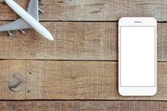 Telefon- och flygplanleksaken på den wood tabellen transporterar affärsidé arkivfoton
