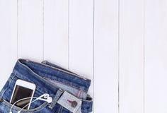 Telefon och hörlur i det Jean facket med vitt kopieringsutrymme Royaltyfria Bilder