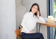 Telefon och leende för härlig ung asiatisk kvinna talande i coffee shop Royaltyfri Fotografi