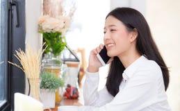 Telefon och leende för härlig ung asiatisk kvinna talande i coffee shop Royaltyfri Foto
