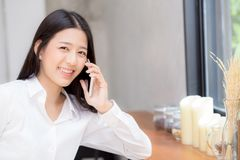 Telefon och leende för härlig ung asiatisk kvinna talande i coffee shop Fotografering för Bildbyråer
