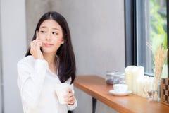 Telefon och leende för härlig ung asiatisk kvinna talande i coffee shop Royaltyfri Bild