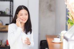 Telefon och leende för härlig ung asiatisk kvinna talande i coffee shop Arkivfoto