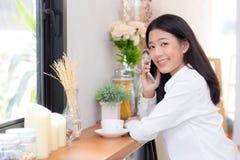 Telefon och leende för härlig ung asiatisk kvinna talande i coffee shop Arkivfoton