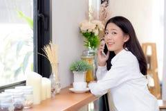 Telefon och leende för härlig ung asiatisk kvinna talande i coffee shop Royaltyfria Bilder