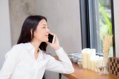 Telefon och leende för härlig ung asiatisk kvinna talande i coffen Fotografering för Bildbyråer