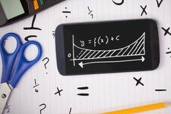 Telefon på en skolatabell med skolasymboler på skärmen Arkivfoto