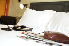 Telefon på säng i hotellrum arkivbild