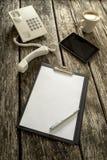 Telefon, pastylka, kawa i papier na stole, Obrazy Stock