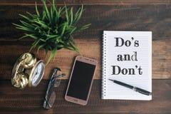 Telefon, szkła, zegar, zielona roślina i notatnik z, Robimy ` s i przywdziewamy ` t słowo obrazy stock
