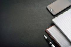 Telefon, Tablette und Notizblock auf dem Tisch Stockfotos