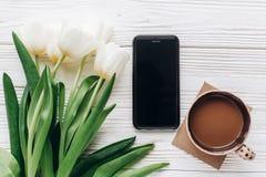 Telefon, tulipany i ranek kawa na białym drewnianym nieociosanym backg Zdjęcie Royalty Free