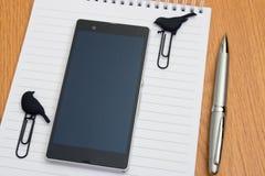 Telefon und Büroklammern auf einem Notizblock Lizenzfreies Stockfoto