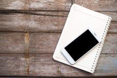 Telefon und Buch auf hölzernem Hintergrund und Tapete Lizenzfreie Stockbilder