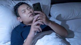 Telefon Uzależniający się, mężczyzna Używa Mądrze telefon na łóżku przy północą obrazy stock