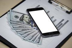 Telefon z białym ekranem jest na dolarach z prześcieradłami z cha zdjęcie stock