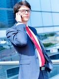 Telefonar dinâmico executivo júnior fora de seu escritório Fotos de Stock Royalty Free