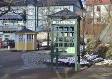 Telefonbås som byggs av trä och exponeringsglas för att passa in med andra wood hus i Vaxholm Royaltyfria Bilder