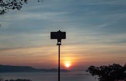 Telefone à manhã da névoa e do sol do fundo após a montanha imagem de stock royalty free