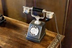Telefone análogo antigo preto na tabela de madeira foto de stock