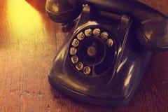 Telefone análogo do vintage antigo preto que disca ou que enrola o telefone na tabela de madeira imagens de stock