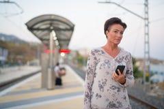 Telefone bonito maduro da terra arrendada da mulher do turista ao esperar no estação de caminhos de ferro imagens de stock royalty free