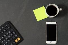 Telefone branco com uma x?cara de caf?, uma pena vermelha e uma mentira da calculadora em uma tabela de madeira branca imagem de stock royalty free