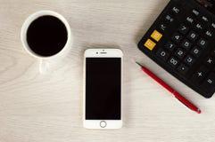Telefone branco com uma x?cara de caf?, uma pena vermelha e uma mentira da calculadora em uma tabela de madeira branca foto de stock royalty free