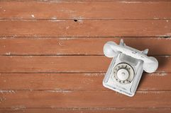 Telefone branco do vintage em uma madeira marrom textured imagem de stock royalty free