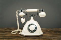 Telefone branco velho na tabela de madeira com fundo da parede da cor fotografia de stock royalty free