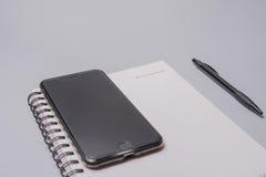 Telefone, caderno e pena espertos na tabela do escritório no fundo branco Conceito do negócio Imagens de Stock Royalty Free