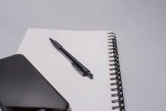 Telefone, caderno e pena espertos na tabela do escritório no fundo branco Conceito do negócio Fotos de Stock